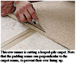 Подпись: This row runner is cutting a looped-pile carpet. Note that the padding seams run perpendicular to the carpet seams, to prevent their ever lining up.